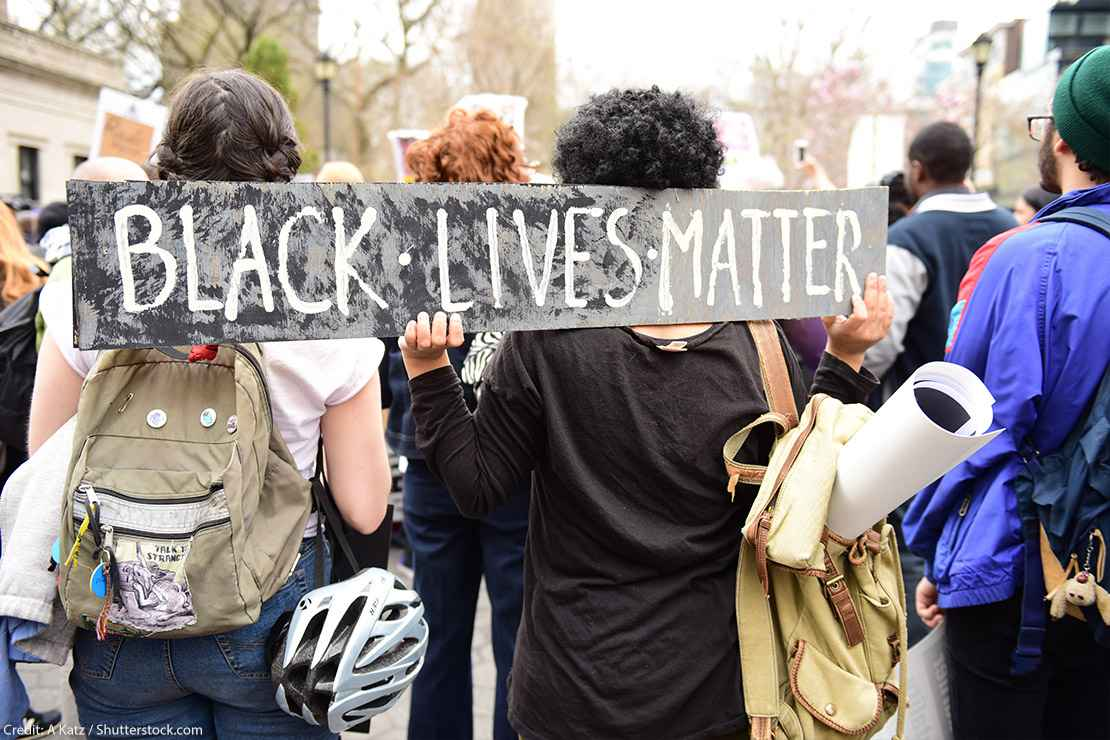 """Protestors hold """"Black Lives Matter"""" sign over their shoulders at a rally in Union Square before marching to Lower Manhattan."""