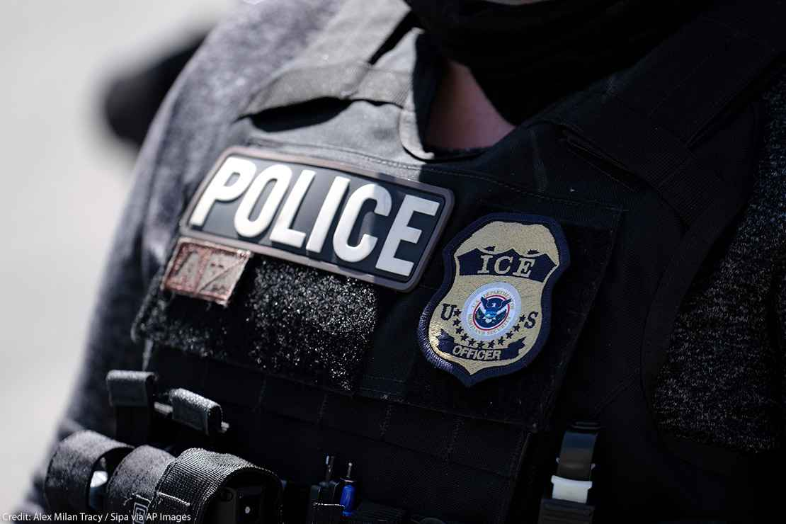 """A close up of a police officer wears a """"Police"""" label beside a U.S. ICE (standing for Immigration and Customs Enforcement) badge on his vest."""