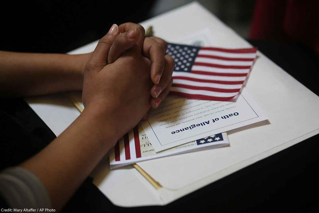 A participant folds her hands of a copy of the Oath of Allegiance and an American flag while listening to speeches during a naturalization ceremony