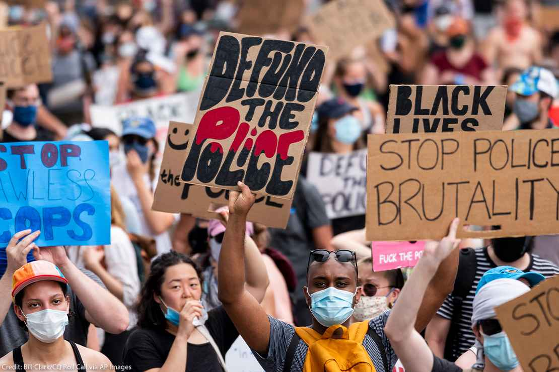 """Protestors march down Pennsylvania Avenue holding signs that read """"Defund the Police"""" and """"Stop Police Brutality"""" among other signs."""
