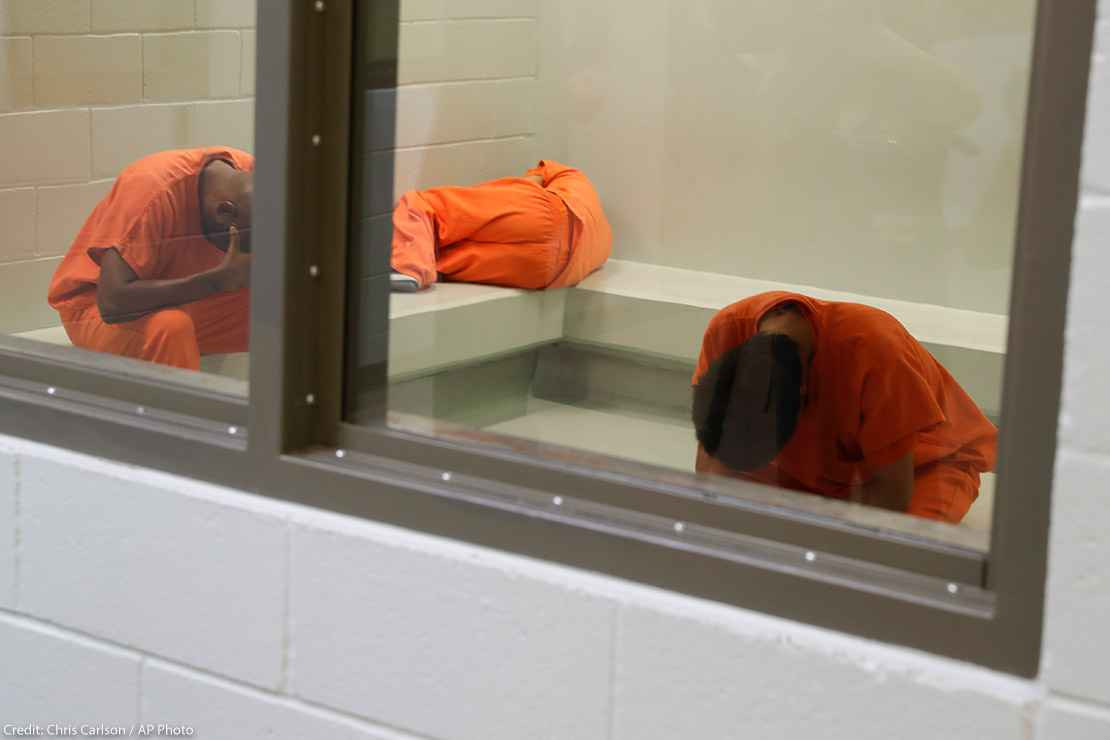 Three detainees waiting together inside a room to be processed at a detention facility.