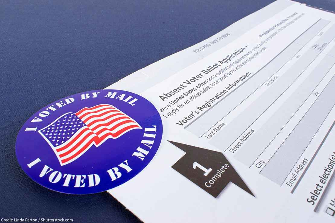 """An absentee voter ballot next to a blue """"I voted by mail"""" sticker."""