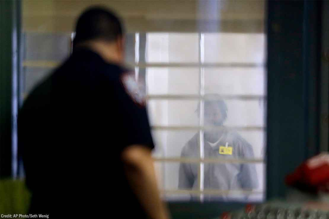 An incarcerated prison looking at a corrections officer separated by bars and a thick plastic barrier.