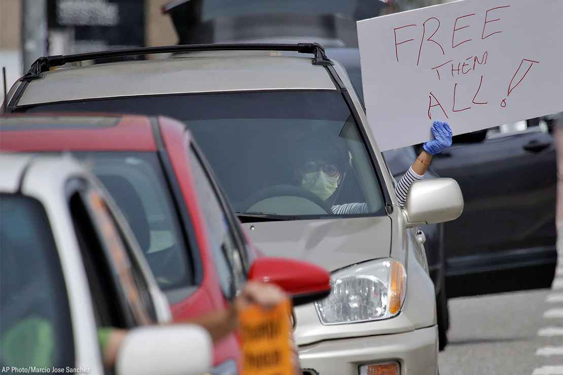 "A demonstrator holds a sign with the text ""Free Them All"" in a car-based protest to demand the release of immigrants in California detention centers over COVID-19 concerns."