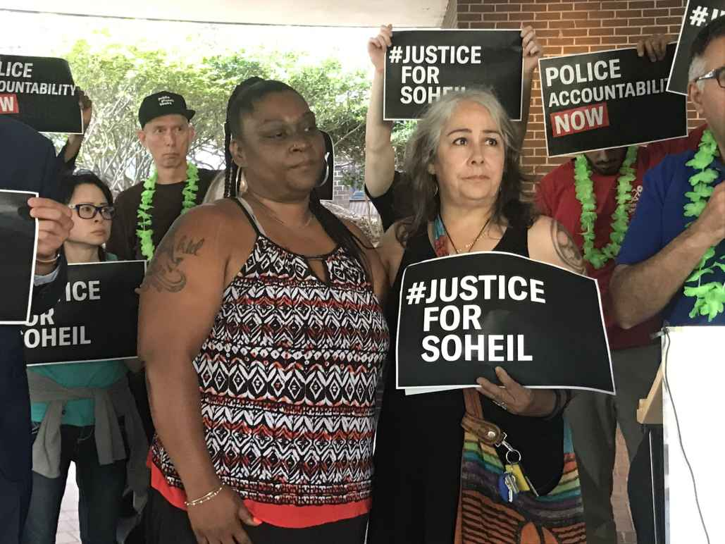 """The mother of Soheil Antonio Mojarrad holds a """"Justice for Soheil"""" sign at a PACT rally"""