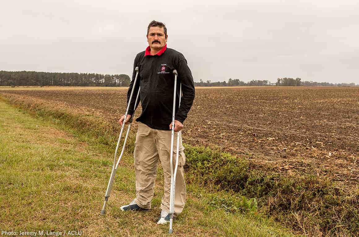 Arturo Hernandez stands on crutches in a field in North Carolina.