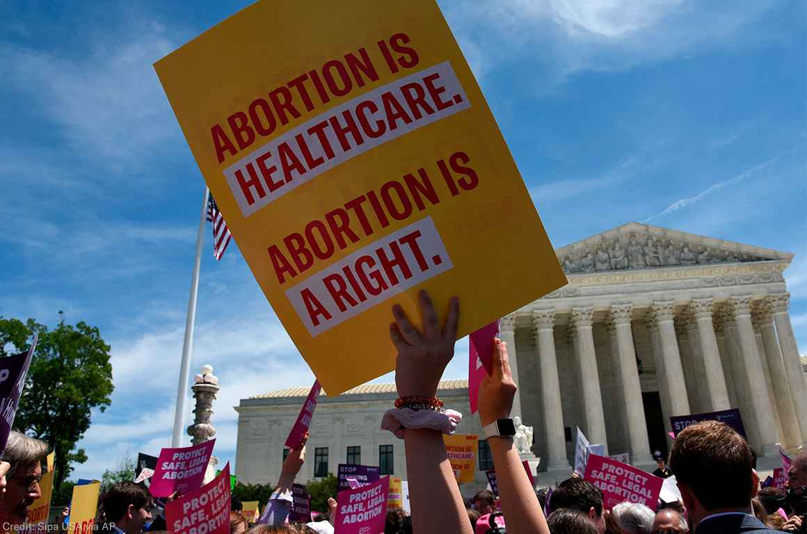 Protesters holding signs at abortion rally in front of Supreme Court