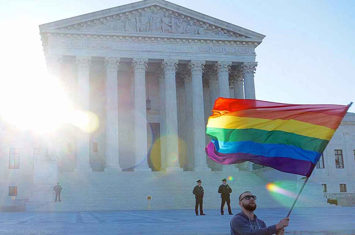 Man waving rainbow flag in front of Supreme Court